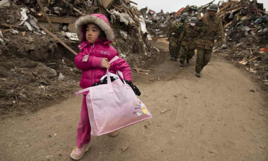 A child carries some family belongings from her home after the earthquake and tsunami in March 2011 in Miyagi province, Japan.