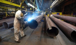 An employee welds the joint on a steel pipe at the SAW Pipe Mills