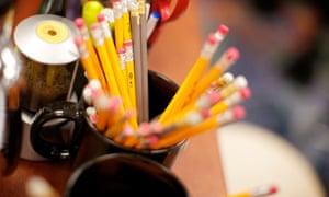 A bunch of pencils in a mug on a teachers desk