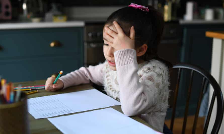 Worried-looking primary school girl working at kitchen table