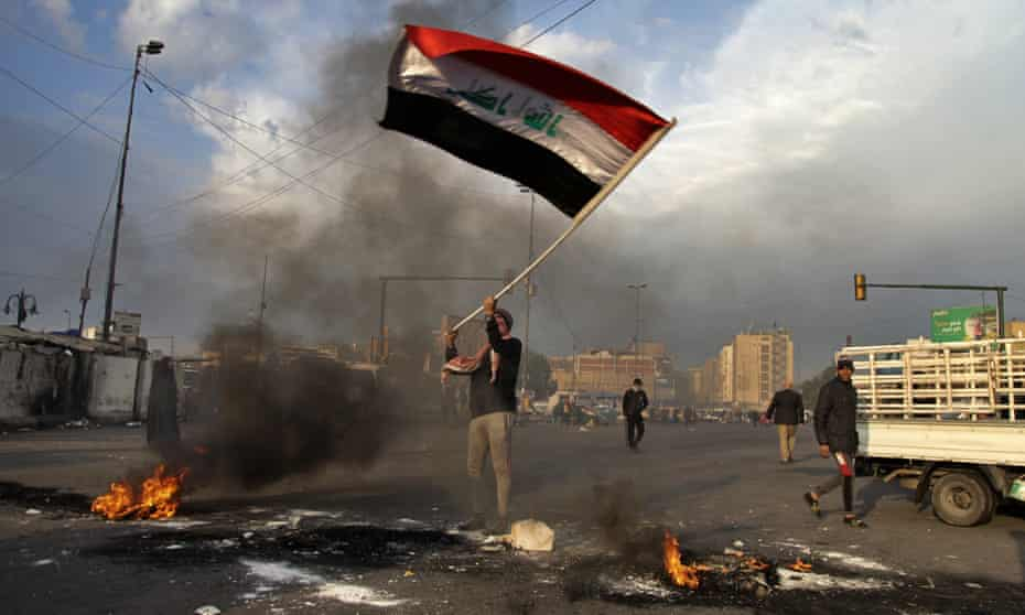 A protester waves the Iraqi flag during a demonstration against the Iranian missile strike in Baghdad.