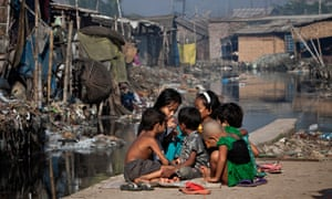 Children play outside their home, next to a polluted canal which empties out into the Buriganga river.
