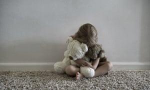 A little girl hugging stuffed toys