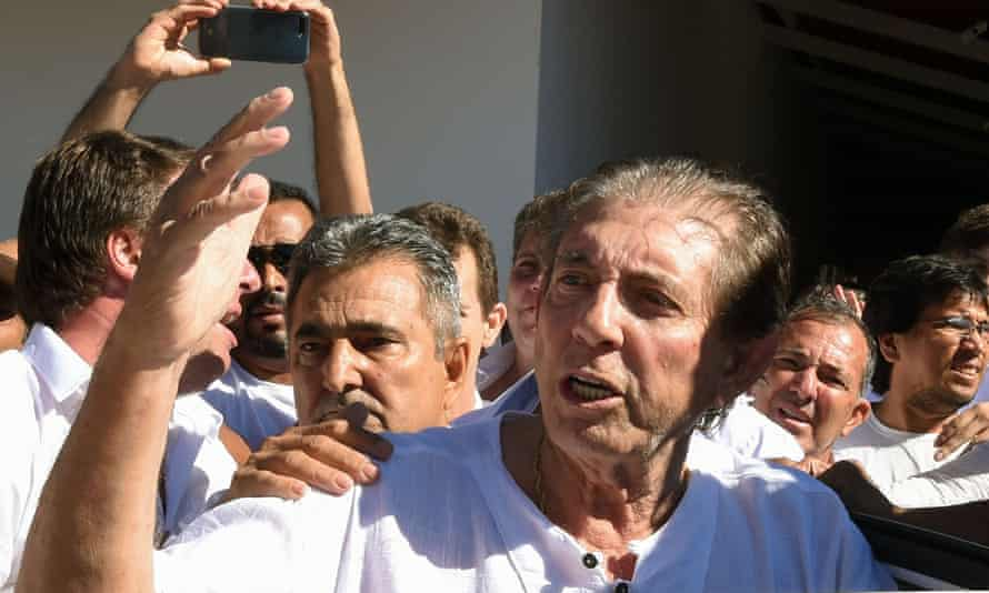 João Teixeira de Faria is escorted by supporters upon arriving at the the Dom Inácio de Loyola house in Abadiânia.