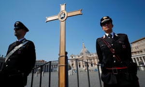 Police officers stand in St. Peter's Square with a cross, as Pope Francis holds his Easter Sunday mass with no public participation.