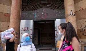 People wearing face masks stand outside the damaged entrance of the Association of Banks in Beirut.