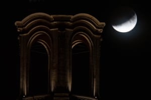 The partially hidden moon behind the Frauenkirche in Dresden, Germany