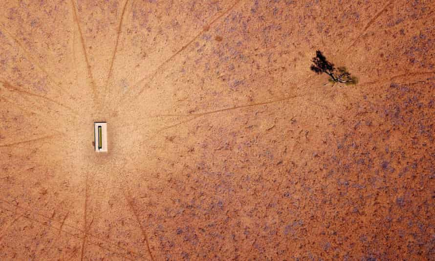 A lone tree stands near a water trough in a drought-affected paddock on Jimmie and May McKeown's property located on the outskirts of town of Walgett, in New South Wales, Australia