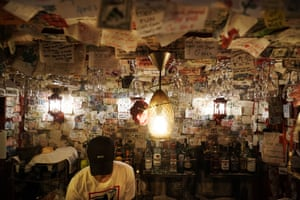 A bartender fixes a drink, surrounded by hundreds of handwritten messages from customers