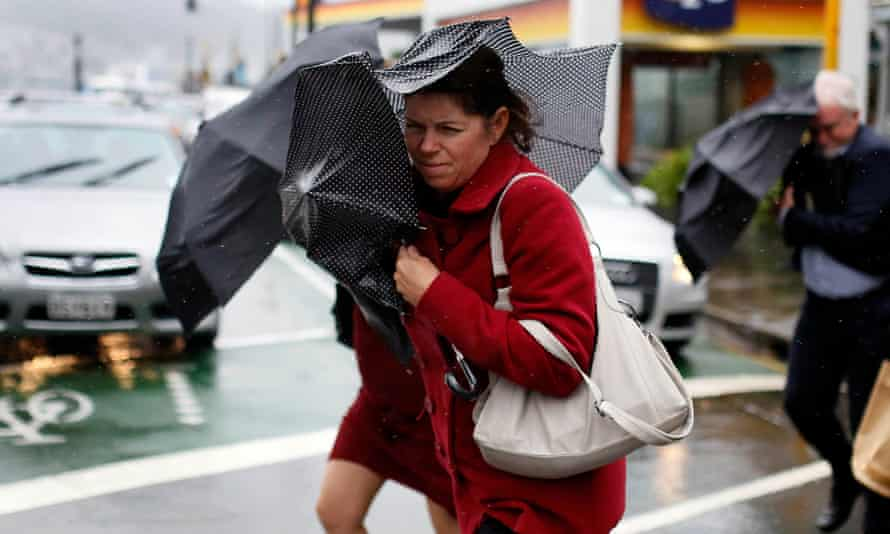 Pedestrians shield themselves from the wind and rain with umbrellas as they cross a road in Wellington