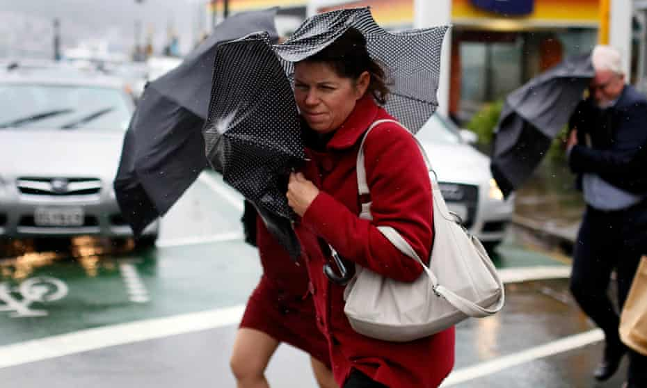Pedestrians shield themselves from the wind and rain with umbrellas as they cross a road during a storm in Wellington