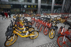 Rows of bicycles from bike-sharing companies wait for users outside an office building in Beijing on Monday.