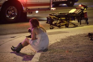 A woman sits on a curb at the scene of the shootings