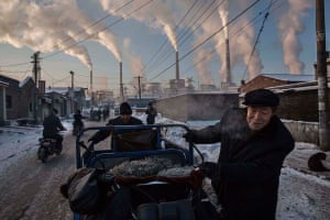 Daily Life, first prize, singles - Kevin Frayer - Chinese men pull a tricycle in a neighborhood next to a coal-fired power plant in Shanxi, China