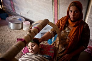 Gamara puts her hand on the head of her four-year-old disabled son, Hathan, in their tent in a camp near Erbil