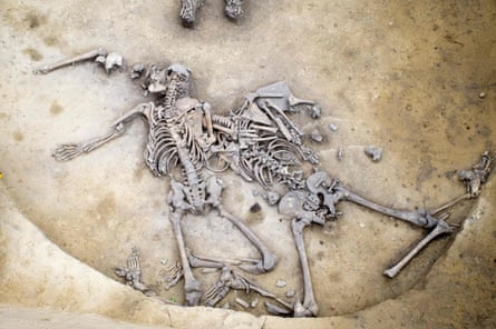 The fossilised skeletons of two men with numerous fractured bones.