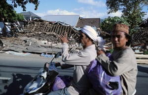 Local people ride past collapsed properties after the earthquake struck northern Lombok.