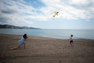 A mother and son play with a toy plane at La Malagueta Beach