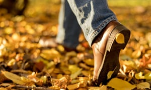 Woman's boots in fallen autumn leaves