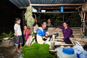 A Dusun family relaxes outdoors after dinner in Kampung Kinapulidan, Borneo, Malaysia