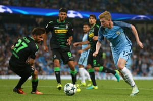 Manchester City's Kevin De Bruyne, right takes the ball past Moenchengladbach's Julian Korb as he attempts to find space for a shot.
