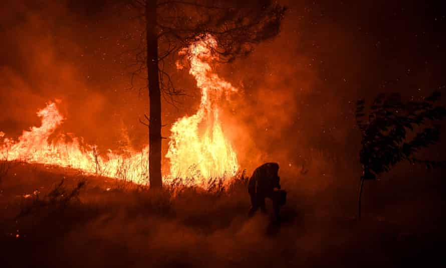 A villager carries a bucket with water as a wildfire encroaches on his home at Amendoa.