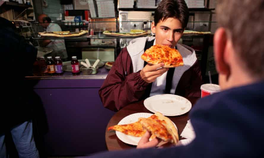 Customers eating pizza in Manhattan, New York