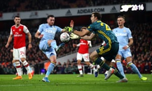 Arsenal's goalkeeper Emiliano Martinez claims the ball just ahead of Jack Harrison of Leeds United.