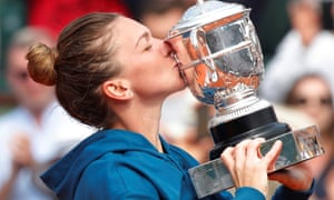 Simona Halep celebrates by kissing the trophy.