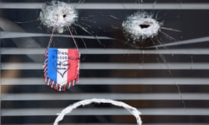 A flag placed by a bullet hole at La Belle Equipe restaurant in Paris