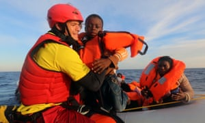 Daniel Calvelo, 26, carries a child into a boat during a rescue operation off the Libyan coast by Spanish NGO Proactiva Open Arms