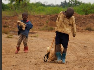 Abraham, 6, and Acili, 4, help their mother Debola Kunda to crush and carry stones. The levels of toxic lead are extreme but she said: 'We know about that but what can we do when there are no others at home to take care of the children? How will we eat if we stay at home.'