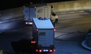 Two migrants cling to the roof of a freight truck as it leaves the Eurotunnel terminal in Folkestone