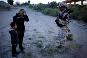 Guatemalan migrant Ledy Pérez reacts while holding hands with her son Anthony while asking to members of the Mexican National Guard to let them cross into the US after traveling 1,500 miles from Guatemala