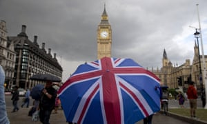 A pedestrian shelters from the rain beneath a union flag umbrella near the Houses of Parliament in London.