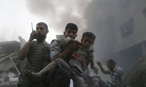 A boy is saved from under the rubble in Douma, Damascus, after what activists say was heavy shelling by President Assad loyalists