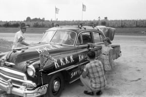 """Ku Klux Klan, Reidsville, Georgia, 1966 A car being decorated for a Knights of the KKK meeting. """"Driving through rural Georgia in 1966, I found to my amazement cars being decorated to go to a party – a Knights of the Ku Klux Klan Meeting. I stopped, overcame my fear, and got permission to follow them to the meeting and a cross rising on the steps of the County Courthouse in Reidsville, Georgia where I completed the photography that night."""""""
