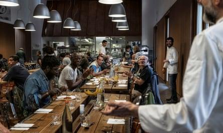 Massimo Bottura (far right) says hello during service at Refettorio Ambrosiano.