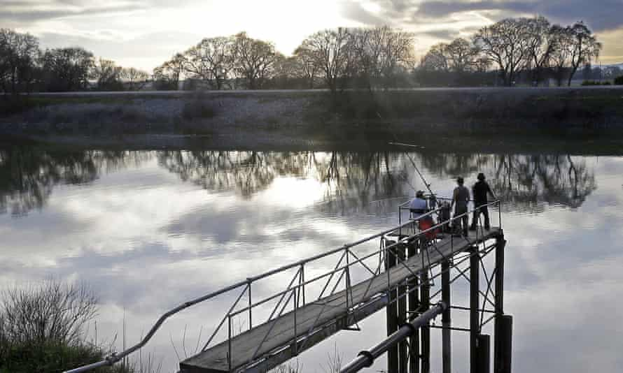 In this Feb. 23, 2016 file photo, people try to catch fish along the Sacramento River in the San Joaquin-Sacramento River Delta, near Courtland, Calif.