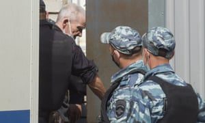 Yury Dmitriev being escorted to court on 22 July.