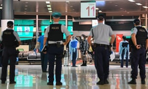 Police officers look on as passengers arrive at Sydney airport.