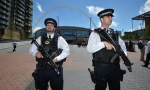 Armed police officers patrol outside Wembley Stadium ahead of the FA Cup final between Arsenal and Chelsea on Saturday