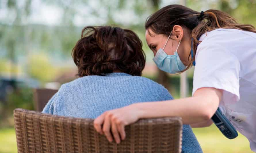 a nurse wearing a mask with an older person
