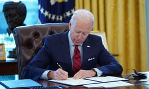 Joe Biden signs executive orders on health care in the White House in Washington DC on 28 January 2021