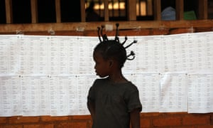 A child stands in front of a  list of voters