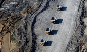 Truk sampah yang sarat dengan pasir minyak melewati sebuah tambang di Alberta, Kanada pada tanggal 4 Juni 2015. Perusahaan pasir minyak Kanada mendera pekerja dan uang.