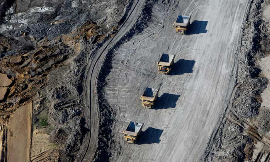 Dump trucks loaded with oil sands drive through a mine in Alberta, Canada on 4 June 2015. Canadian oil sands companies are hemorrhaging both workers and money.