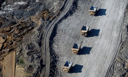 An aerial view of four vehicles in a barren mining landscape