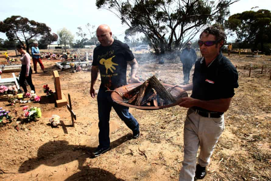 Jason Kelly (left) takes the ceremonial fire to the site of the ceremony.