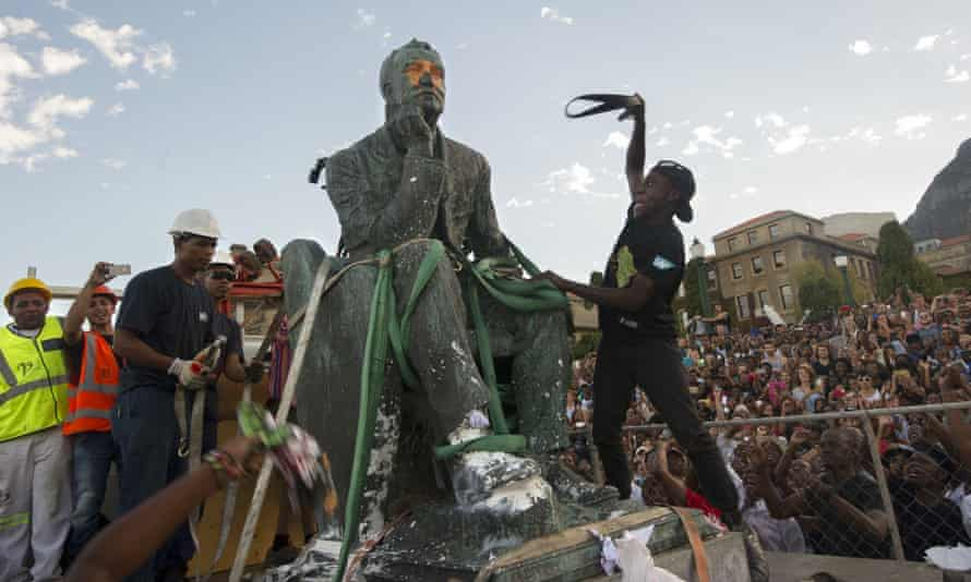 Students attack the defaced statue of British mining magnate and politician Cecil John Rhodes as it is removed from the University of Cape Town in April 2015.
